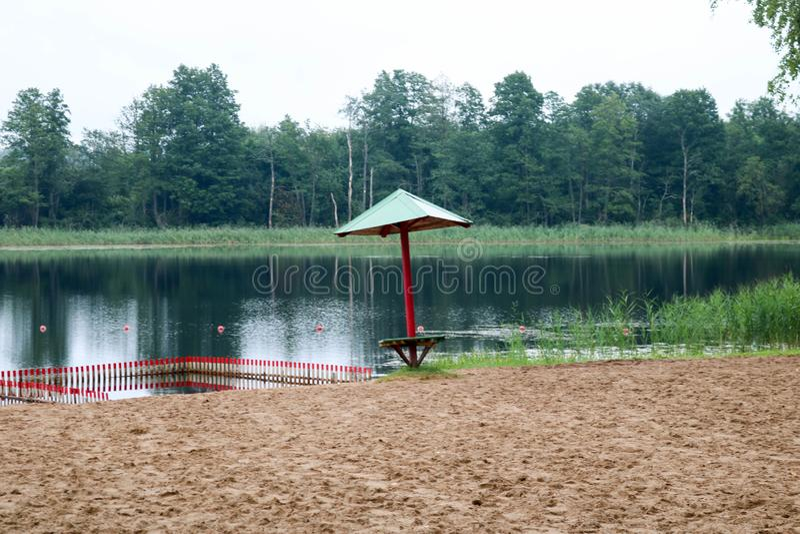 Um solitário, guarda-chuva afundado de cessão e cerco, um cercadinho para banhar crianças em um Sandy Beach na costa de um lago,  foto de stock