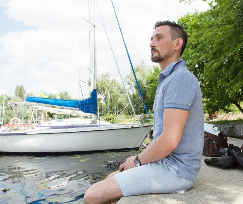 Um sonho de relaxamento do homem e apreciando da vista na natureza e no lago Homem novo considerável que levanta fora no porto foto de stock royalty free