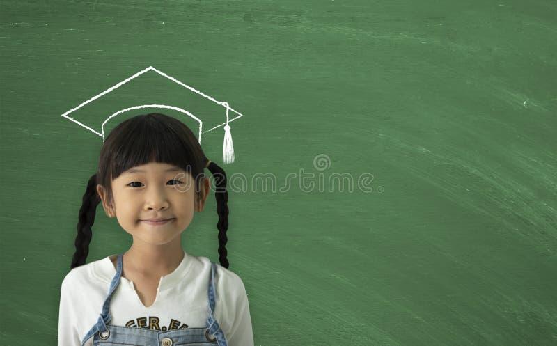 Um sorriso feliz da menina asi?tica pequena no fundo do quadro De volta ao conceito da escola imagens de stock