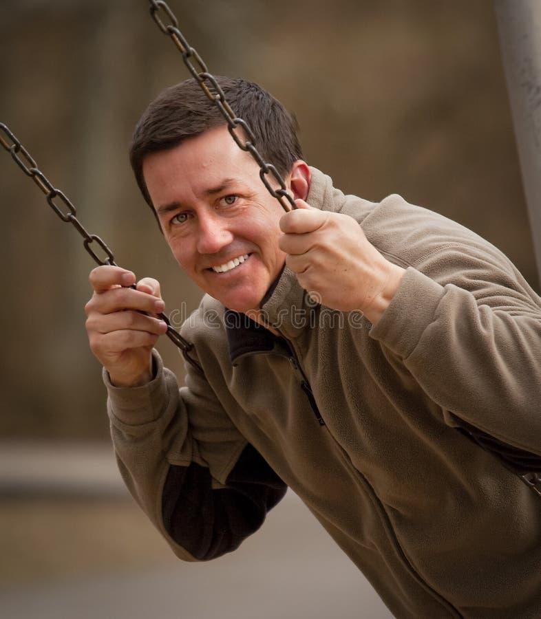 Homem considerável, sorrindo no balanço foto de stock