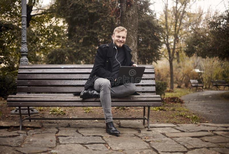 Um sorriso novo e homem feliz, sentando-se no parque do banco em p?blico, usando o port?til, fotos de stock royalty free