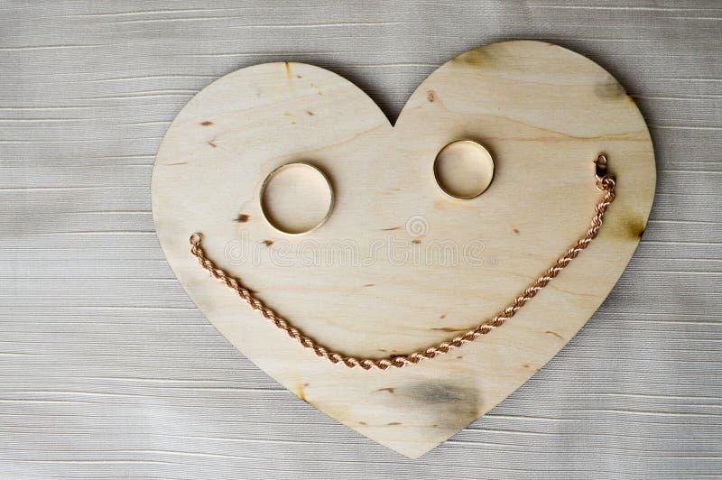 Um sorriso, uma cara alegre, amável feita de um coração de madeira para o dia do ` s do Valentim, uns anéis de ouro do casamento  foto de stock royalty free