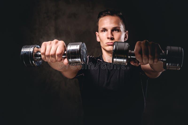 Um sportswear vestindo do halterofilista novo que faz o exercício com pesos no fundo escuro foto de stock
