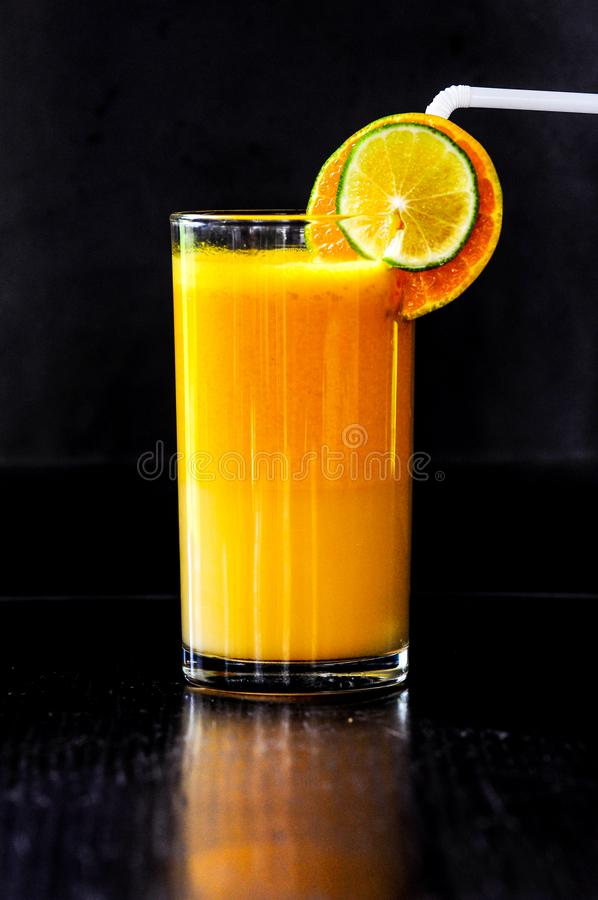 Um suco de laranja com fundo preto fotografia de stock