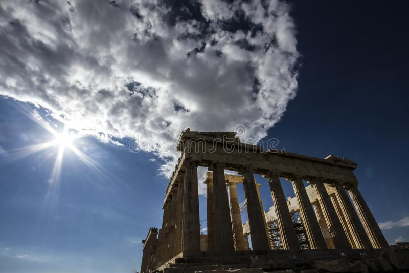 Um sunstar é mostrado contra o céu grego azul profundo acima do Partenon de Atenas foto de stock royalty free