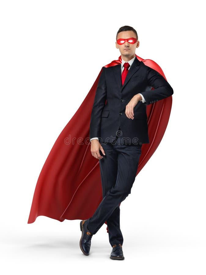 Um super-herói em um terno de negócio e em um cabo vermelho que inclinam-se em um objeto invisível no fundo branco fotografia de stock royalty free