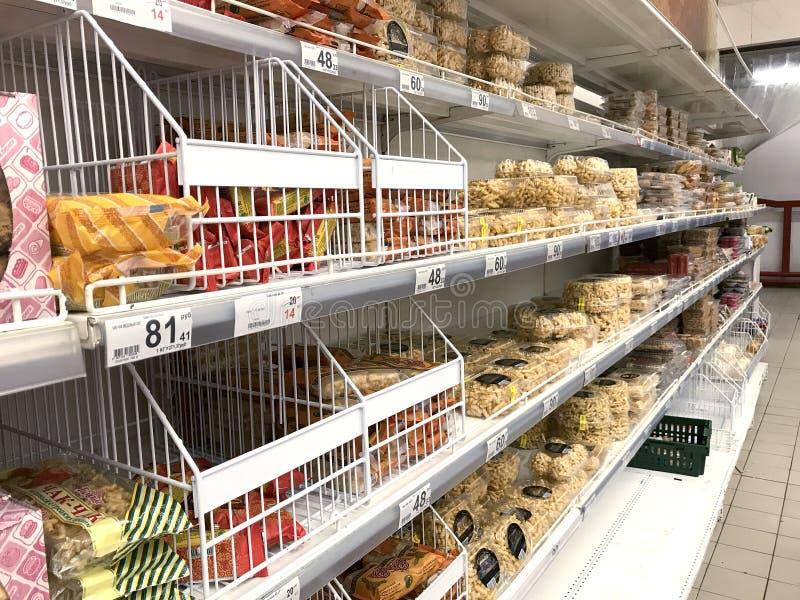 Um suporte com mantimentos, biscoitos e bolos no hipermercado de Auchan foto de stock