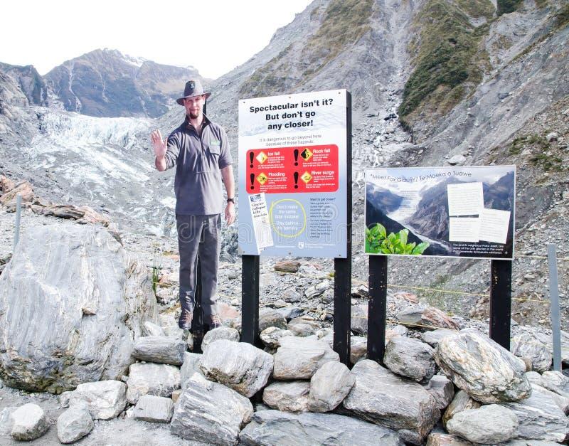 Um suporte da foto do homem mostra o regulamento do sinal de aviso para a queda de gelo, queda da rocha, inundação, impulso do ri foto de stock royalty free