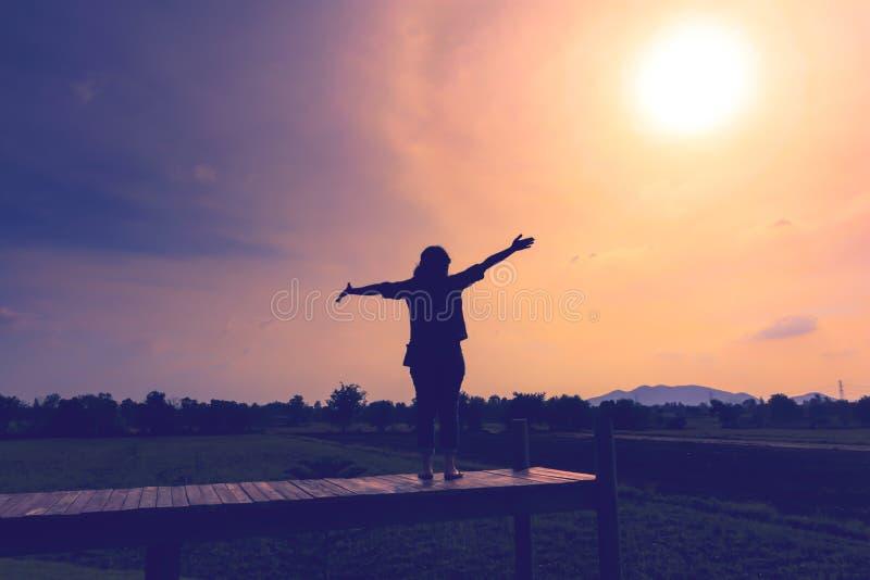 Um suporte feliz da mulher arma-se para considerar o sol fotos de stock