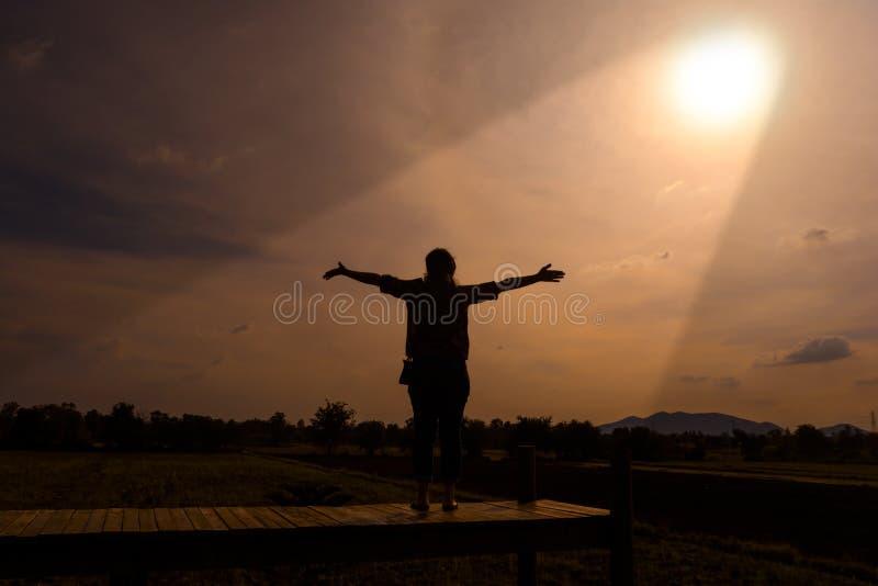 Um suporte feliz da mulher arma-se para considerar o sol imagem de stock