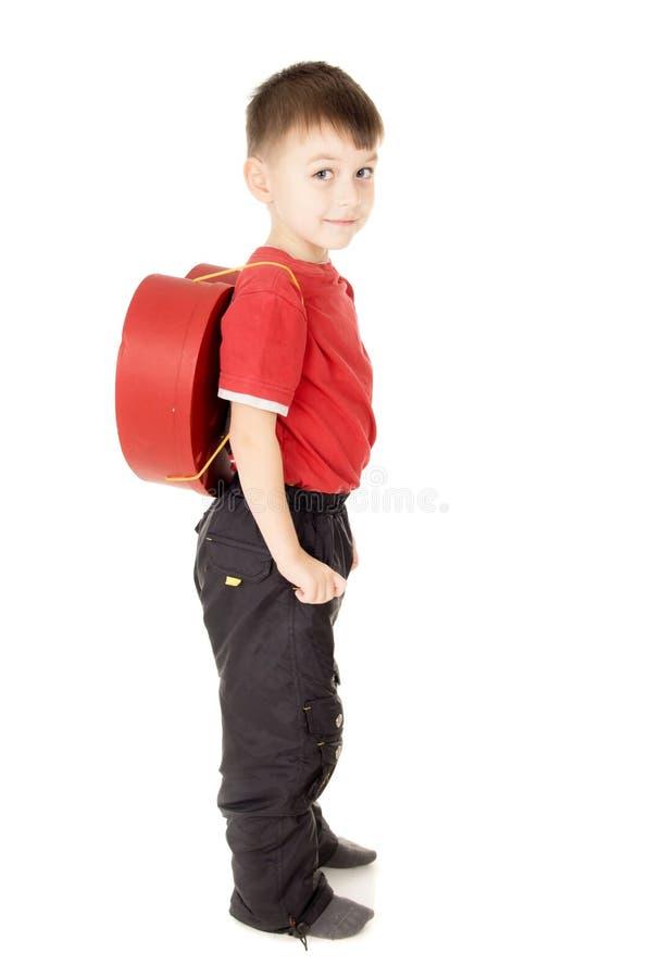Um suporte pequeno da criança é com uma trouxa sob a fôrma do coração imagem de stock royalty free