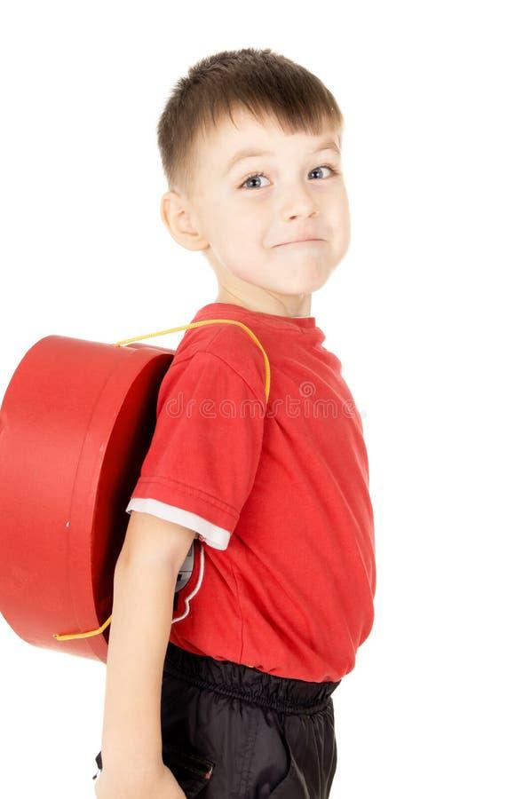 Um suporte pequeno da criança é com uma trouxa sob a forma do coração imagens de stock royalty free