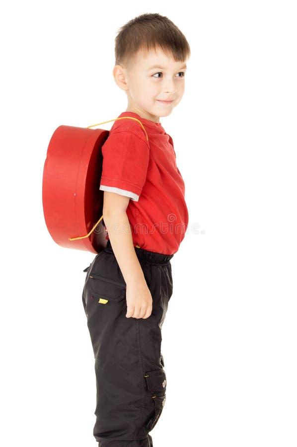Um suporte pequeno da criança é com uma trouxa sob a forma do coração fotos de stock