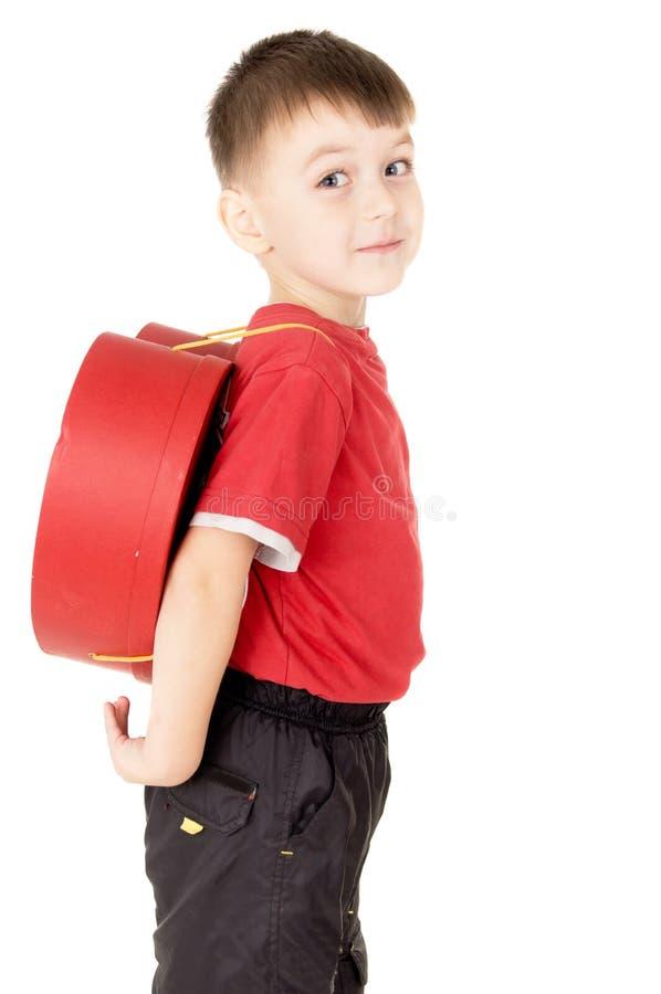Um suporte pequeno da criança é com uma trouxa sob a forma do coração imagens de stock