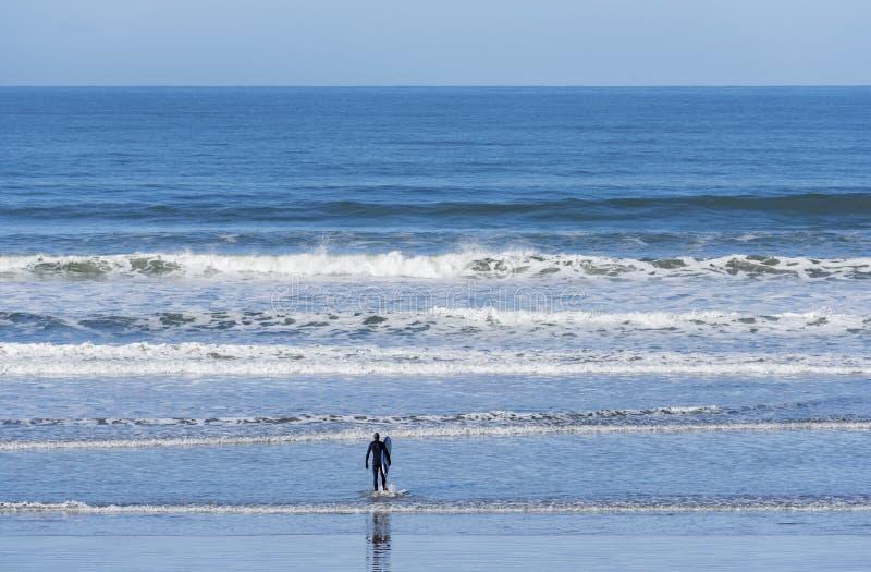 Um surfista apenas na frente do Oceano Pacífico fotografia de stock