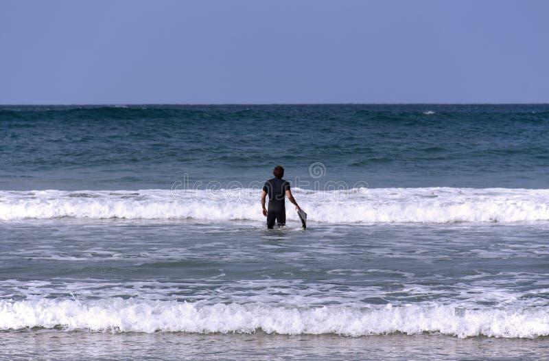 Um surfista com sua placa que entra no mar foto de stock