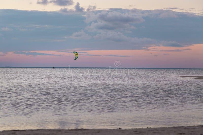 Um surfista do papagaio para fora no oceano durante o por do sol em Isla Blanca, QR, México imagem de stock