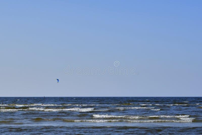 Um surfista do paraquedas navega distante para fora ao mar em um dia ventoso próximo foto de stock