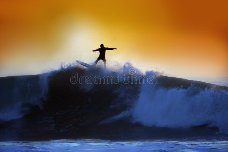 Um surfista que monta uma onda grande no por do sol fotos de stock royalty free