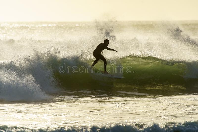 Um surfista que surfa na praia da baía do ` s de Betty no por do sol no cabo ocidental, África do Sul fotos de stock