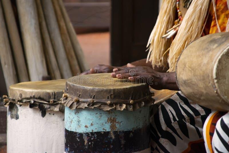 Um tambor africano tocando em um tambor no dia foto de stock