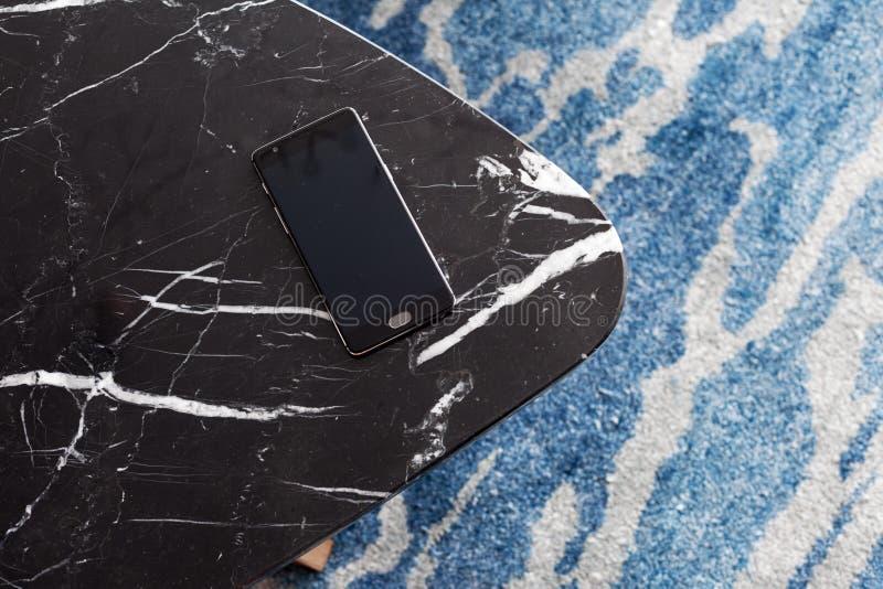 Um tamborete feito da pedra artificial está em um tapete com sesta fina, uma vista superior O telefone celular encontra-se em um  foto de stock