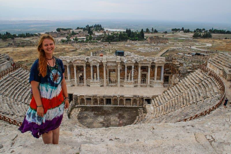 Um teatro grego antigo clássico em Pamukkale, em Denizli, em Turquia e em uma jovem mulher branca em um vestido da hippie foto de stock