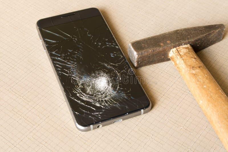 Um telefone celular e um martelo quebrados no fundo cinzento fotografia de stock royalty free