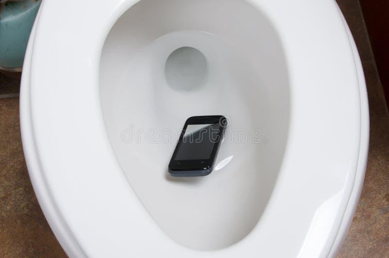 Um telefone celular no toalete imagens de stock royalty free