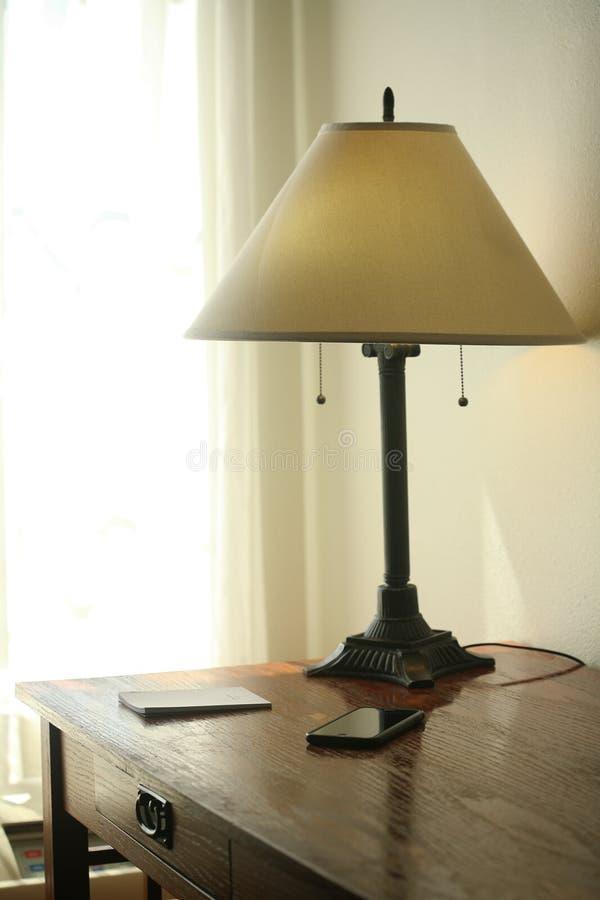 Um telefone celular, uma lâmpada e uma almofada de memorando em uma mesa imagem de stock royalty free