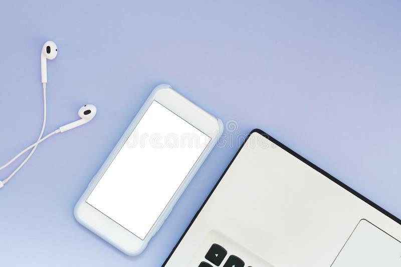Um telefone com uma tela branca, um portátil e os fones de ouvido em um fundo azul Dispositivos e lugar lisos da configuração par fotografia de stock