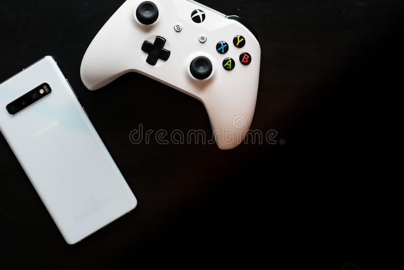 Um telefone e um controlador sentam-se de lado a lado enquanto o jogo se transforma multi-plataforma foto de stock royalty free