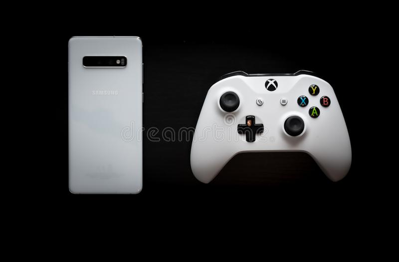 Um telefone e um controlador sentam-se de lado a lado enquanto o jogo se transforma multi-plataforma fotos de stock royalty free