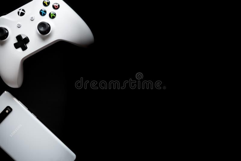 Um telefone e um controlador sentam-se de lado a lado enquanto o jogo se transforma multi-plataforma fotografia de stock royalty free