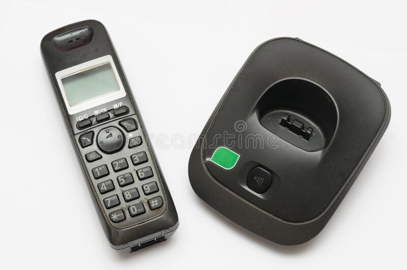 Um telefone sem fio usado, com sua unidade de suporte de desligamento contra um pano de fundo branco foto de stock royalty free