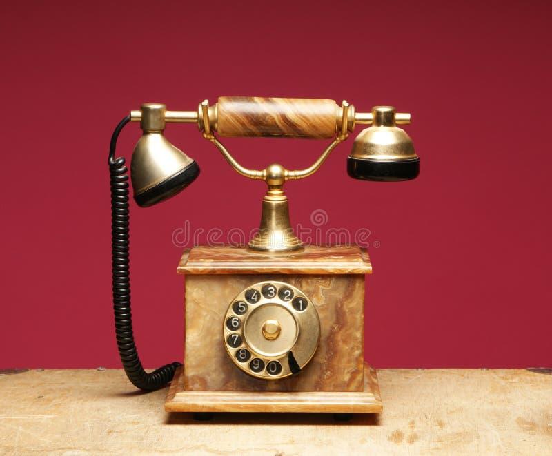 Um telefone velho e do vintage em um fundo vermelho foto de stock royalty free