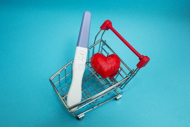Um teste de gravidez positivo e um coração vermelho em um carrinho de compras foto de stock royalty free
