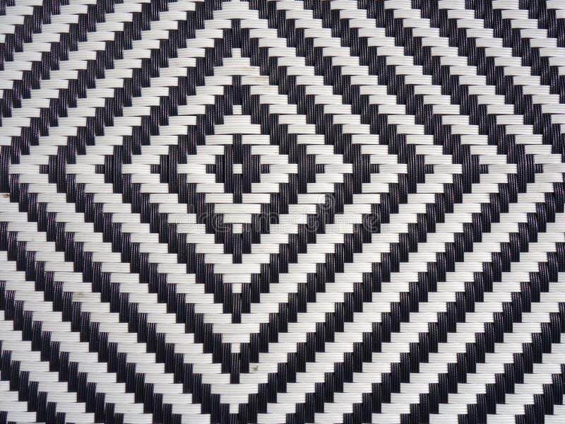 Um teste padrão preto e branco do diamante formou no plástico tecido como um fundo imagens de stock