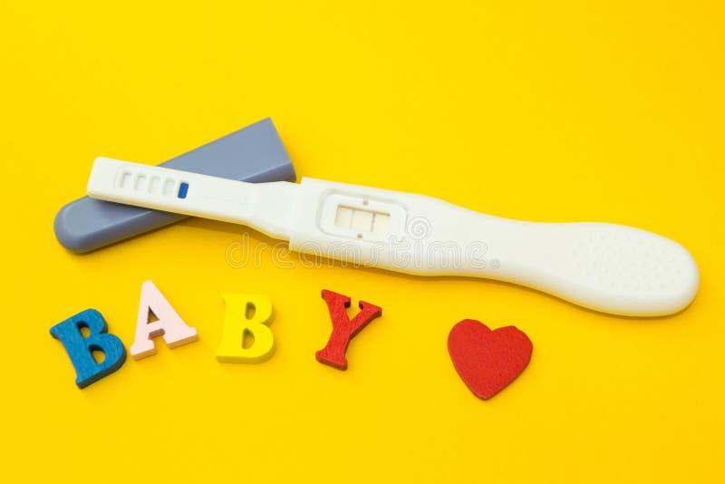 Um teste positivo para a gravidez, o coração e a palavra 'bebê 'em um fundo amarelo fotografia de stock