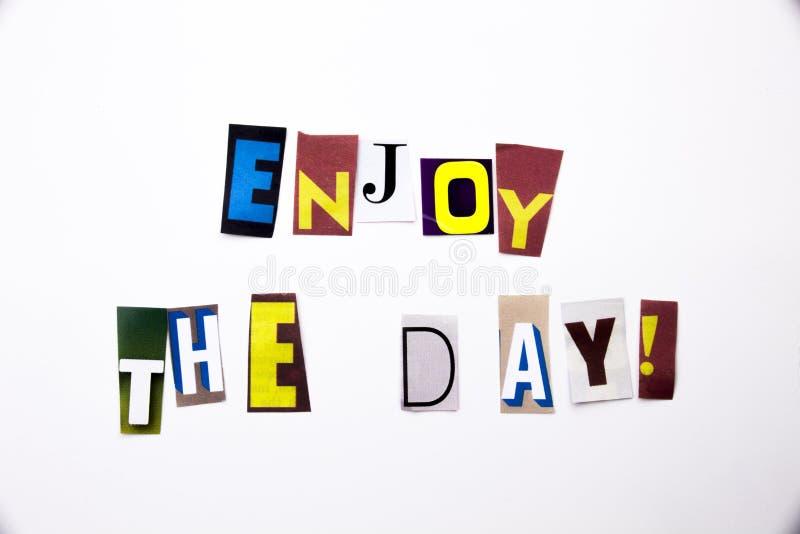 Um texto da escrita da palavra que mostra a conceito Enjoy o dia feito da letra diferente do jornal do compartimento para o caso  foto de stock royalty free