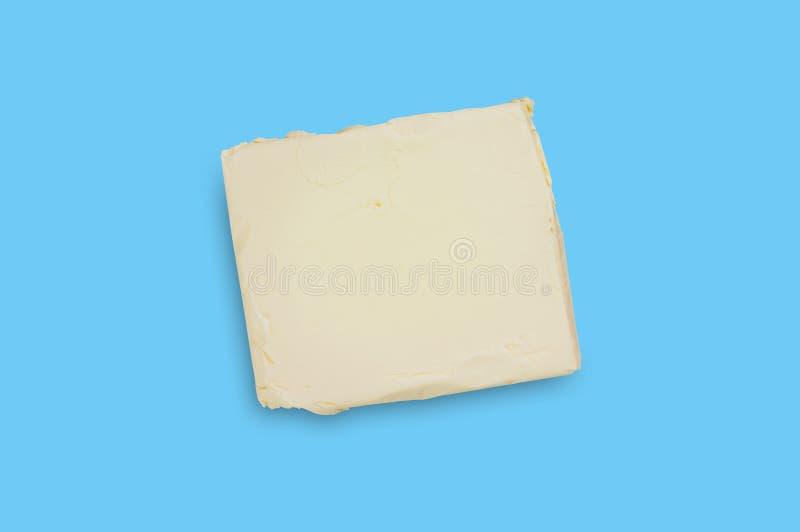 Um tijolo da manteiga ou da margarina gorda no centro da tabela azul na cozinha Vista superior fotografia de stock