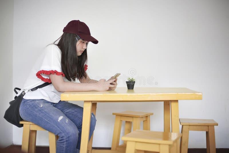 Um tipo de assento mensagens do adolescente em telefones celulares foto de stock