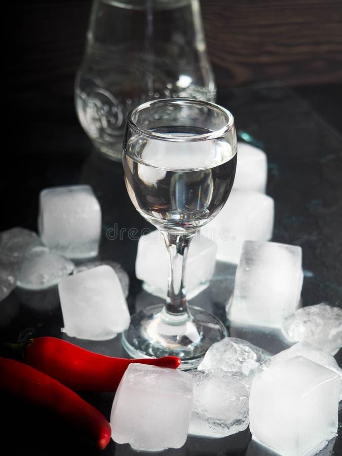 Um tiro da vodca, uma bebida alcoólica, ao lado do gelo, fogo, gelo, pimenta de pimentão vermelho O conceito do álcool, espírito imagens de stock royalty free