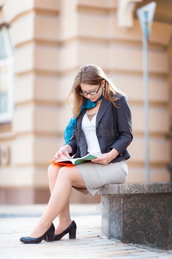 Um tiro de uma estudante universitário que lê um livro no ar livre fotografia de stock