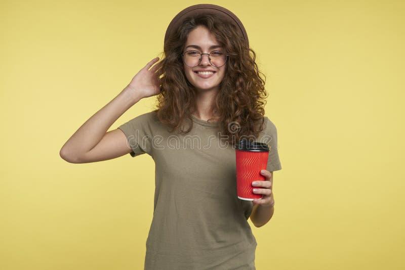Um tiro do estúdio da mulher nova do estudante, sorri e mantendo um copo de café, um chapéu vestindo e uns monóculos, isolados so fotografia de stock royalty free
