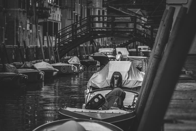Um tiro do preto e do whtie das gôndola estacionadas no lado de um rio estreito em Itália imagens de stock