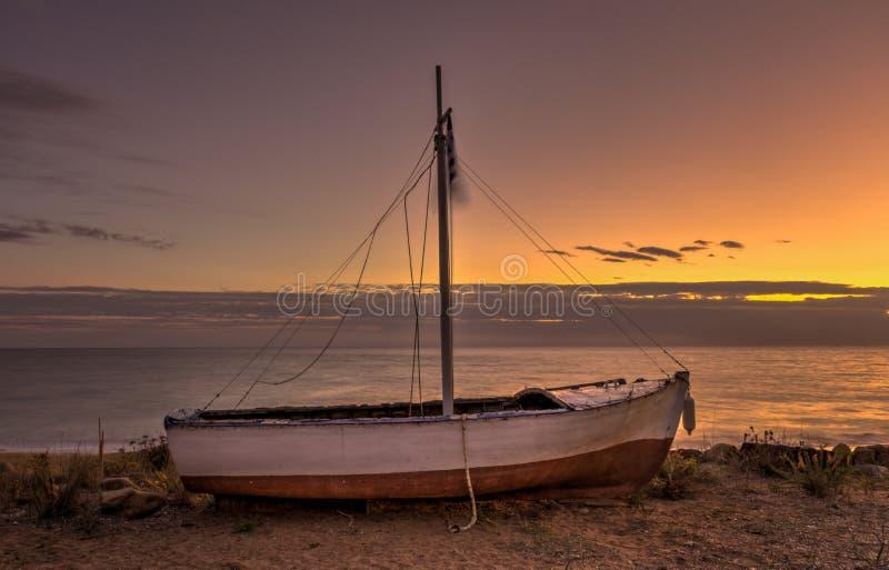Um tiro longo da exposição de um grego encalhou o barco de pesca na praia durante o por do sol imagem de stock royalty free