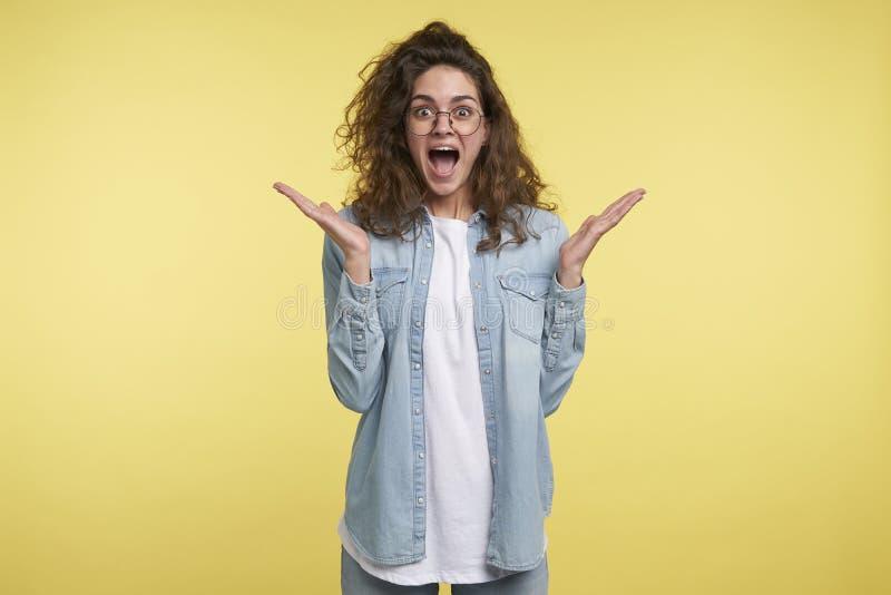 Um tiro médio da mulher moreno gritando feliz com cabelo encaracolado, sobre o fundo amarelo imagem de stock royalty free