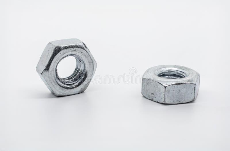 Um tiro macro de duas porcas de encontro do ferro imagem de stock