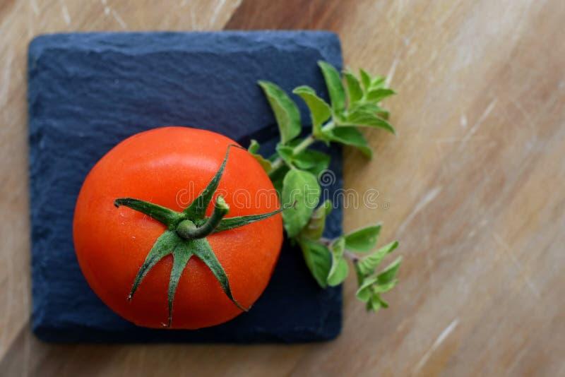 Um tomate do grappolo com oréganos fotos de stock